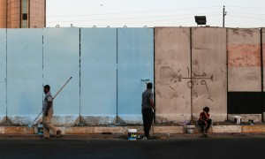 Workers paint blast walls in Baghdad. Photograph: Sam Tarling