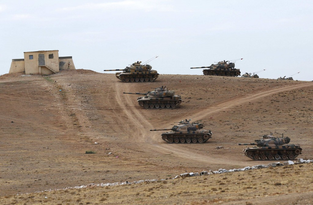 Turkish army tanks take up position on the Turkish-Syrian border near the southeastern town of Suruc in Sanliurfa province September 29, 2014. Turkish tanks and armoured vehicles took up positions on hills overlooking the besieged Syrian border town of Kobani on Monday as shelling by Islamic State insurgents intensified and stray fire hit Turkish soil, a Reuters correspondent said. At least 30 tanks and armoured vehicles, some with their guns pointed towards Syrian territory, were positioned near a Turkish military base just northwest of Kobani. Plumes of smoke rose up as shells hit the eastern and western sides of Kobani and sporadic bursts of machinegun fire rang out. REUTERS/Murad Sezer (TURKEY - Tags: POLITICS CONFLICT MILITARY TPX IMAGES OF THE DAY)