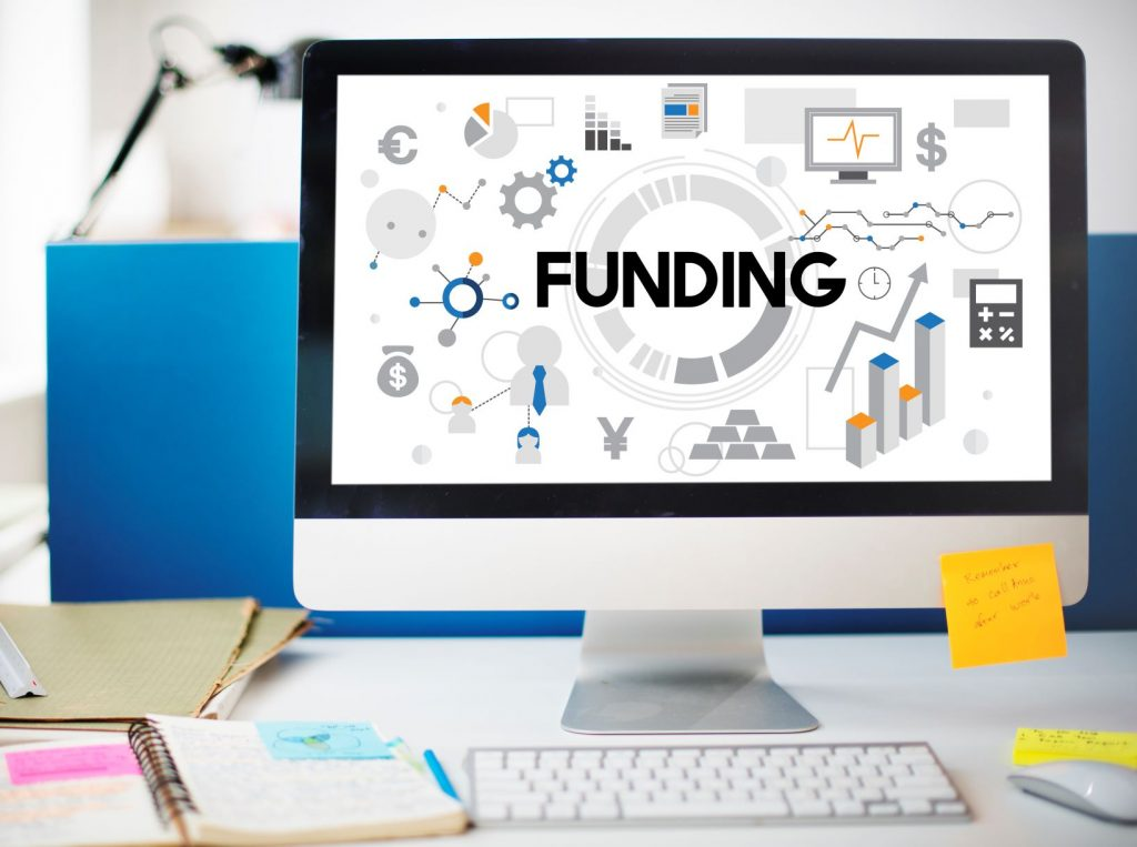 Stock image of a computer with an image that spells out the word funding on screen