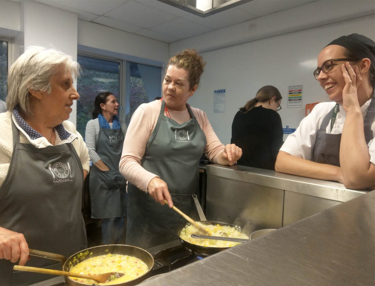 A picture of 3 ladies in aprons preparing food and chatting