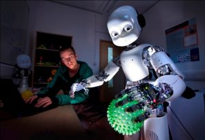 Dr Martin Peniak with a Humanoid Robot that is holding a ball